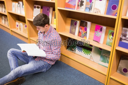 young man reading book while sitting