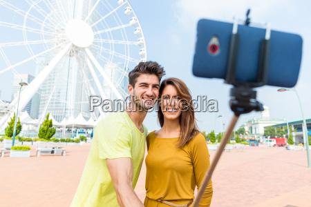 pareja caucasica utilizar el palo selfie