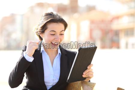 euforico ejecutivo exitoso viendo una tableta