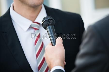 periodista tomando entrevista de empresario