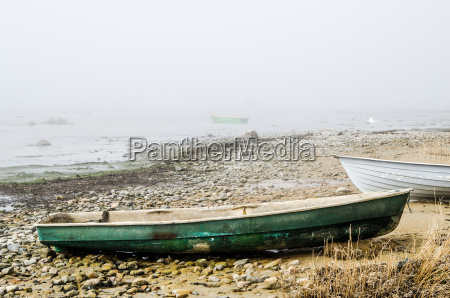 old fishing boat at coast foggy