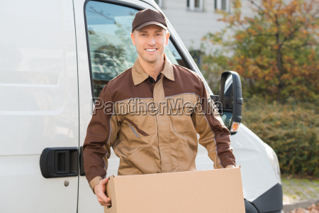 delivery man carrying cardboard box with