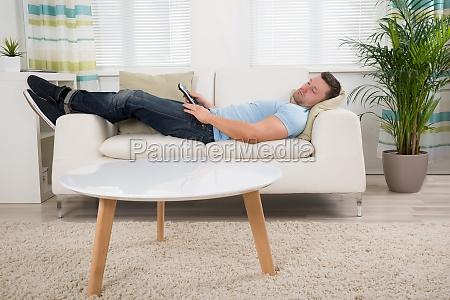 hombre con control remoto durmiendo en