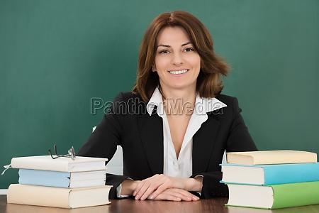 profesora sentada en la mesa de