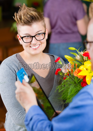 female flower shop customer paying