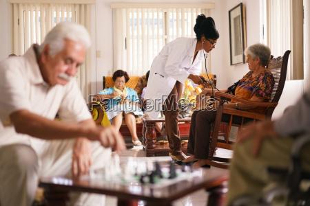 medico de hospicio midiendo la presion
