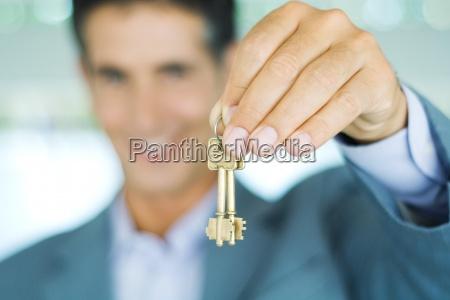 hombre en traje sosteniendo las llaves