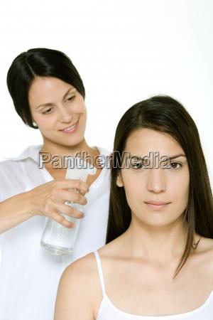 estilista usando botella de aerosol para