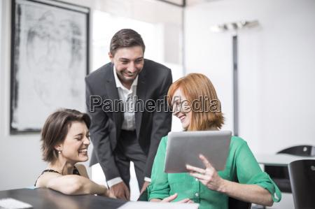 forretningskvinde viser digital tablet til griner