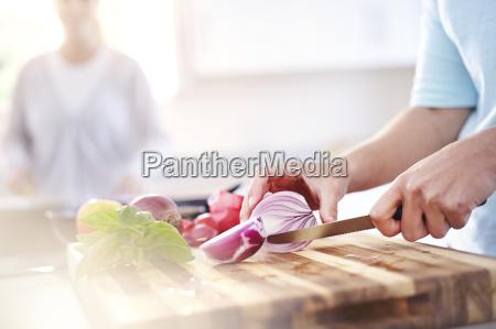 mujer que rebana la cebolla roja