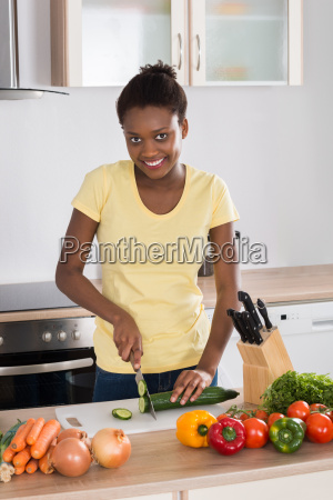happy woman chopping vegetables
