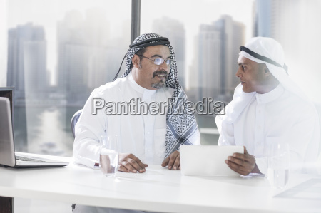 two middle eastern businessmen sitting office