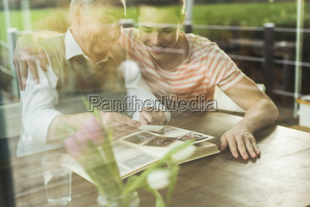 grandfather and grandson watching old photographies