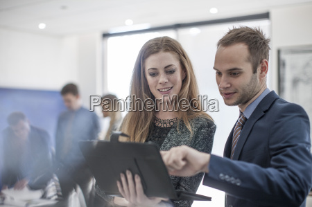 businessman and woman in office looking