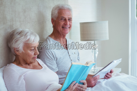 happy senior man with wife reading