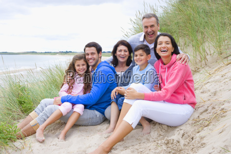 multi generation family smiling on sand