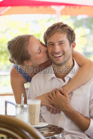 portrait of woman kissing man at