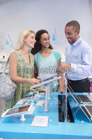 store manager assisting two female customers