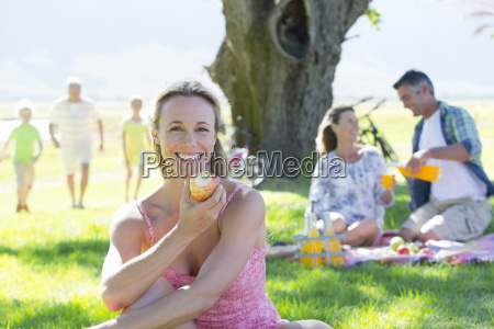 woman eating apple with multi generation