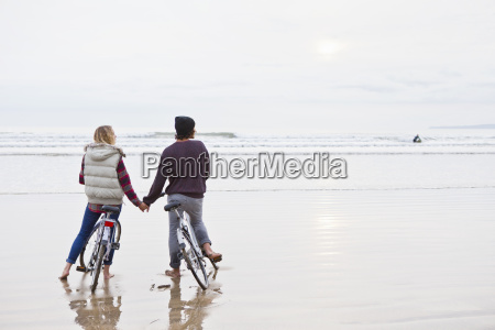 couple with bicycles holding hands looking
