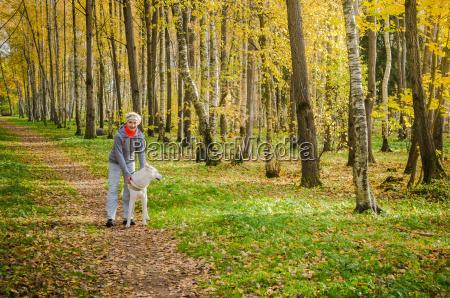 mujer con perro caminando en el