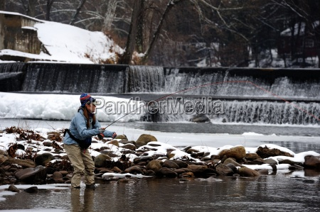 a young lady fly fishing on