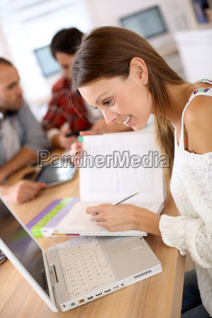 chica en clase estudiando con laptop