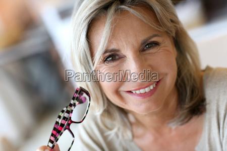 smiling senior woman holding eyeglasses