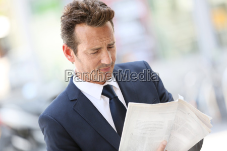 handsome businessman in town holding newspaper
