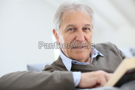 senior man reading book relaxed in