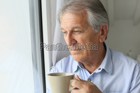 senior man looking by window holding