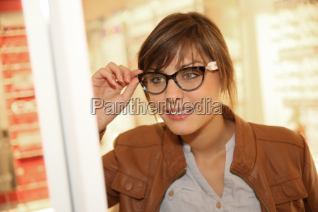 young woman in optical store trying