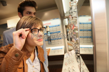young couple in optical shop trying