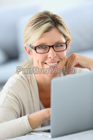 mature woman with eyeglasses websurfing on
