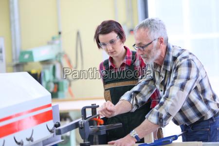 carpintero mostrando a aprendiz como utilizar