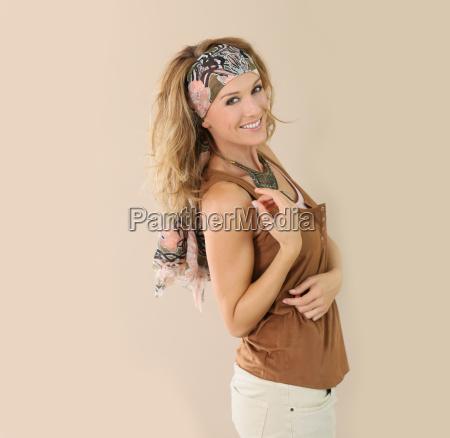 mature stylish woman standing on beige