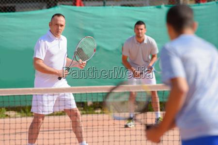 hombres jugando dobles de tenis