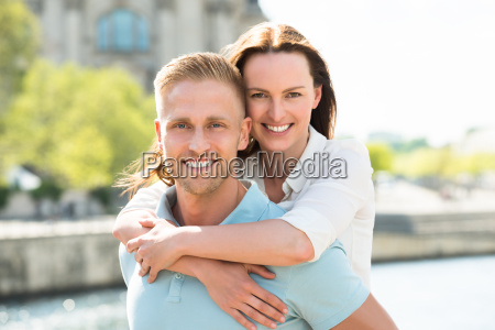 happy man carrying woman on his