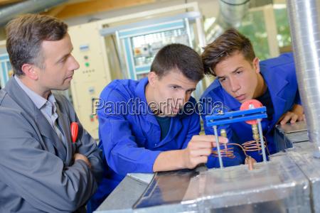 profesor mirar dos estudiantes uso aparato