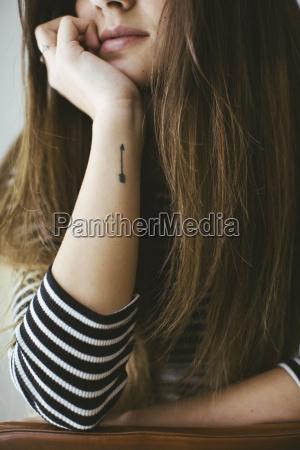 mujer joven con tatoo de flecha