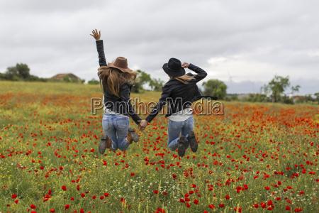 dos mujeres saltando campo de amapola
