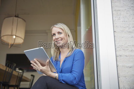 woman sitting in office using digital