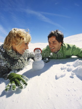 couple laying on snow looking at
