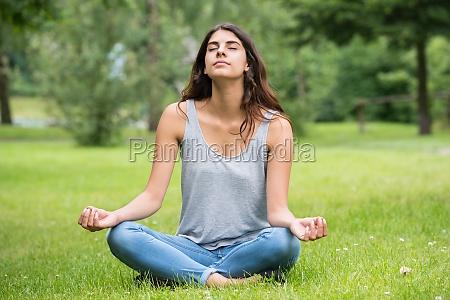 mujer parque jardin pensar meditacion yoga