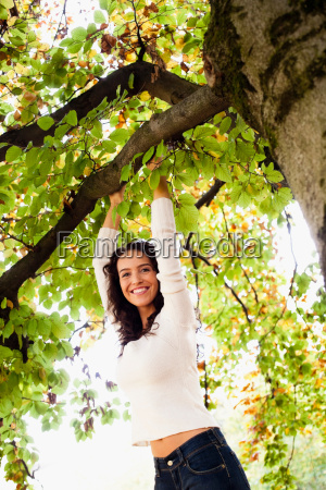 young woman hanging on tree