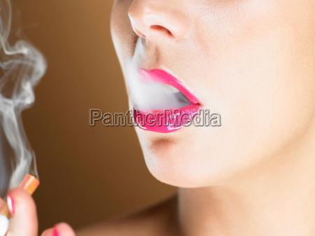 woman in pink lipstick smoking