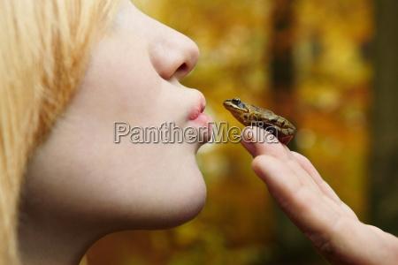 chica besando pequenya rana en el