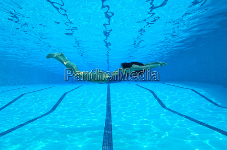 woman swimming in pool underwater view
