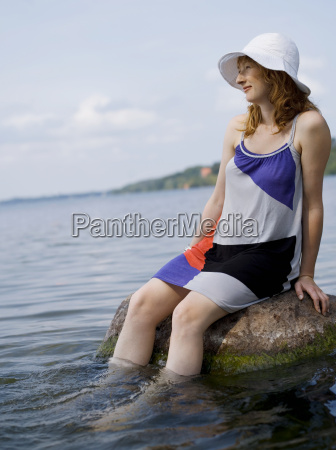 woman sitting on rock in water