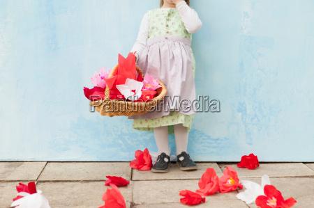 chica sosteniendo cesta de flores de